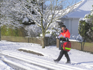 A Royal Mail Postman delivering letters in the snow