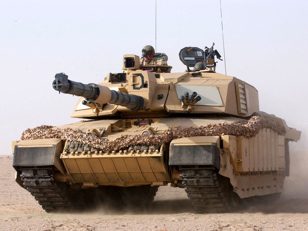 A British Challenger tank driving through the desert.