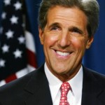John Kerry pictured wearing a red tie in front of the Stars and Stripes (US / USA flag) with pink lips / pink lipstick ?