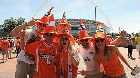 A group of Blackpool fans dressed in orange traffic-cone hats with cans of beer outside the new Wembley stadium before the 2010 Coca Cola Championship play off final against Cardiff