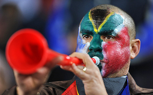 A fan with South Africa face-paint blowing a vuvuzela, the horn from the 2010 South Africa World Cup (vuvuzelas)