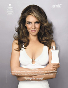 Elizabeth Hurley (Liz Hurley) got milk?  poster dressed in white with a glass of milk and a milk moustache (mustache) and nice cleavage