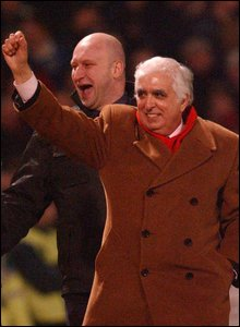 A Jubilant Sam Hamman resplendent in a Brown double-breasted overcoat and red scarf