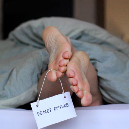 A man's feet protruding from the base of a duvet with a Do Not Disturb sign hanging around his big toe