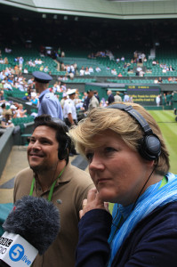 Clare Balding on centre court at Wimbledon wearing headphones with a BBC Radio 5Live microphone and Dom Joly in the background