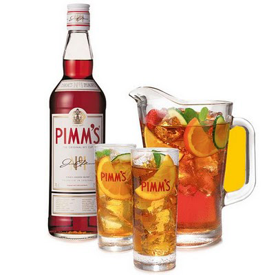 A Pimm's bottle with two Pimm's glasses and a full Pimm's jug.  Fruit too.